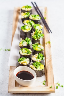 Sushi végétalien vert roule sur une planche de bois.