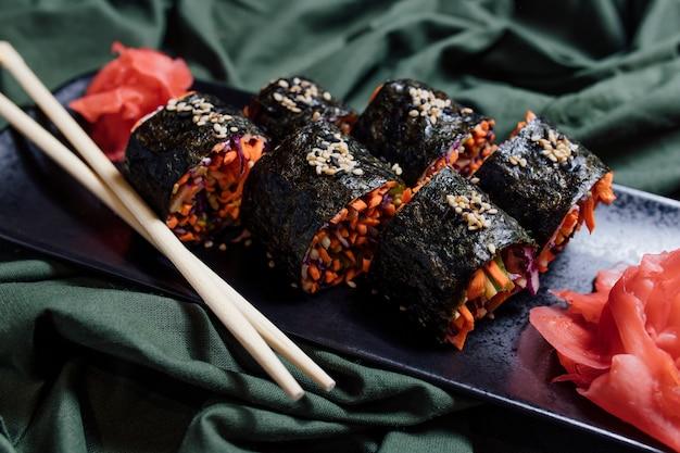 Sushi végétarien et baguettes sur plaque