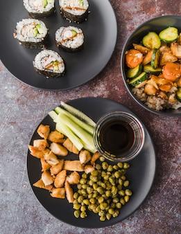 Sushi vue grand angle avec assiettes de légumes