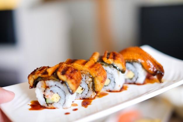 Des sushis anago (grill eel) ou unagi avec sauce japonaise sont servis sur une assiette blanche.