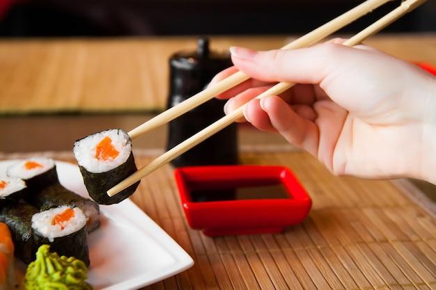 Les sushis gardent les baguettes et les trempent dans la sauce