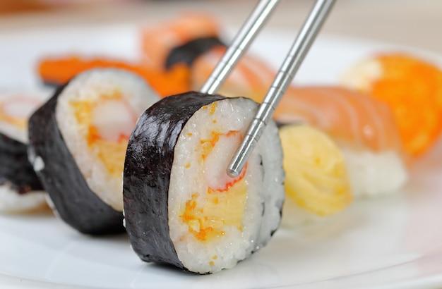 Les sushis gardent les baguettes et trempés dans la sauce.