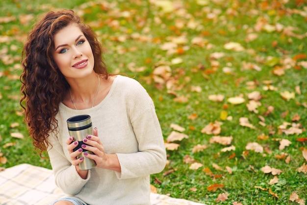 Svelte belle jeune femme se reposant à l'automne dans le parc et assis sur la pelouse sur la pelouse et boire du thé à partir d'un thermocup