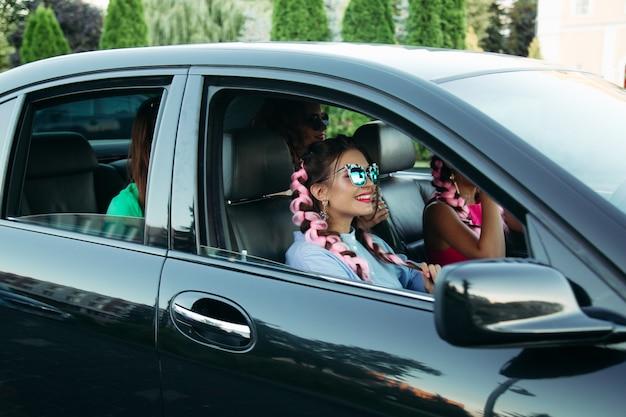 Swag et amies à la mode conduisant et voyageant en voiture noire.