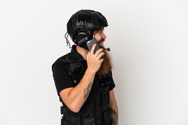 Swat rousse isolé sur fond blanc en gardant une conversation avec le téléphone portable avec quelqu'un
