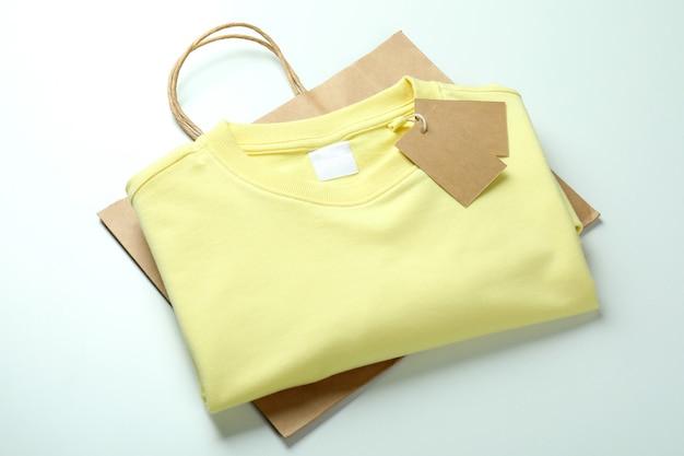 Sweat avec étiquettes et sac sur fond blanc