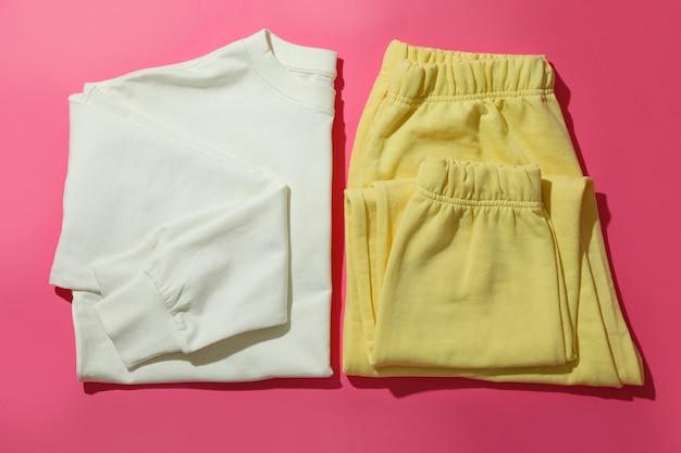 Sweat-shirt plié et pantalon de jogging sur une surface rose