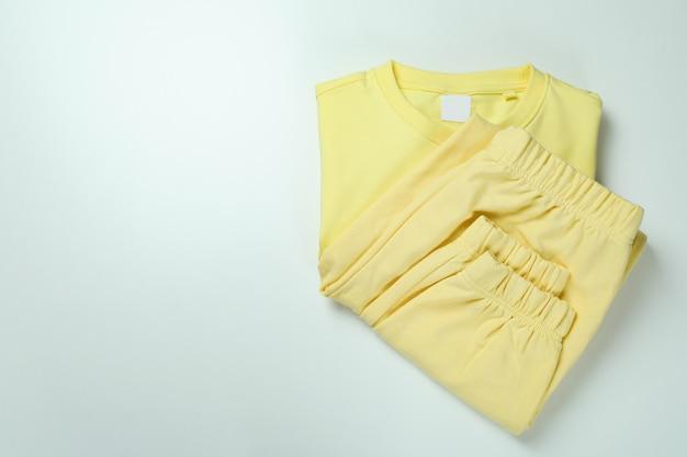 Sweat-shirt plié et pantalons de survêtement sur une surface blanche