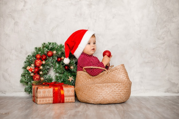 Sweet baby santa est assis dans un panier en osier avec une boîte-cadeau