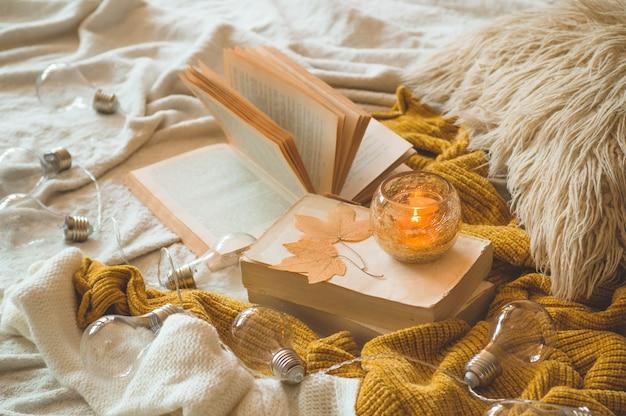 Sweet home. détails de la vie encore à l'intérieur de la maison du salon. chandails et bougie, décor d'automne sur les livres. lisez, reposez-vous. concept d'automne ou d'hiver confortable.