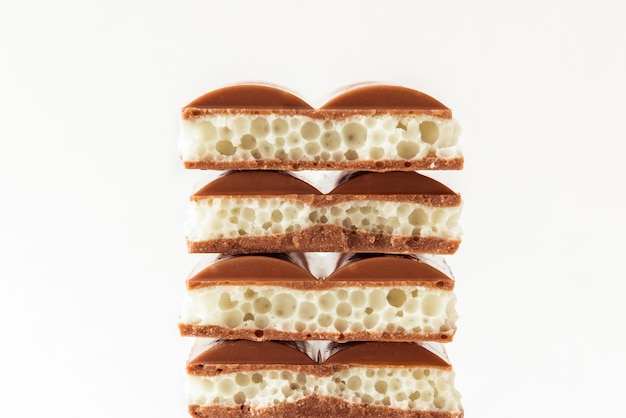Sweet pile de différents types de morceaux de chocolat poreux sur fond blanc