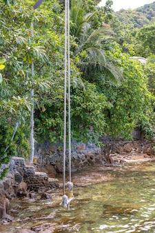 Swing pendre d'un arbre tropical sur une plage de sable près de la mer dans le jardin, île de koh phangan, thaïlande. concept d'été, de voyage, de vacances et de vacances