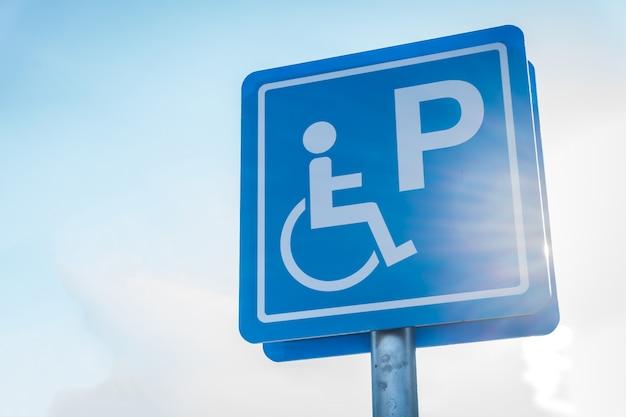 Symbole bleu de stationnement pour handicapés dans le parking avec flou artistique au soleil