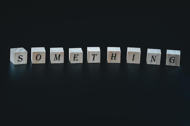 Symbole de blocs de bois avec les mots «quelque chose» sur un beau fond noir.