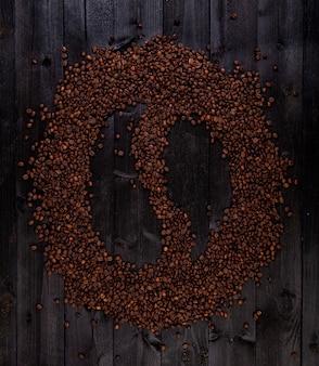 Symbole de café fait de grains de café torréfiés sur un bois noir
