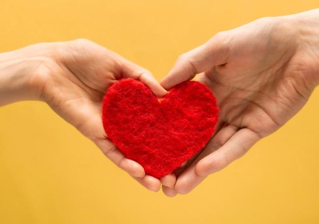 Symbole du coeur des amoureux entre les mains d'un homme et d'une femme concept de la saint-valentin.