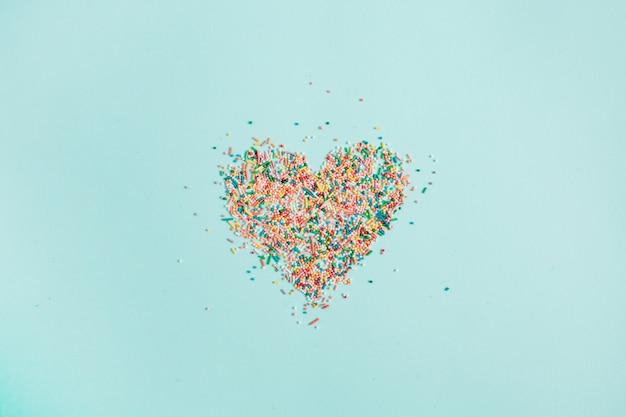 Symbole du coeur coloré fait de confettis sur bleu