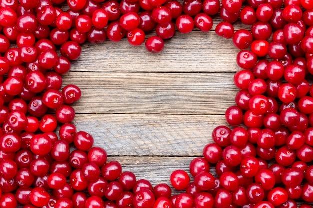 Symbole du cœur fabriqué à partir de baies de cerise sur fond de bois