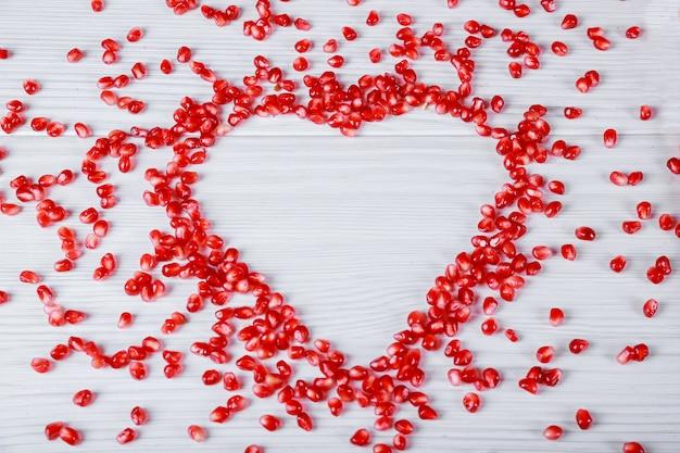 Symbole du coeur fabriqué à partir de graines de grenade sur fond blanc