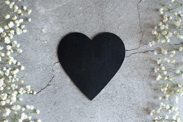 Symbole du coeur fait de flovers et de feuilles. main masculine tenant une dernière fleur.