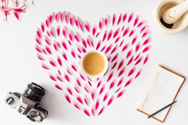 Symbole du coeur fait de pétales de fleurs roses avec appareil photo vintage et ordinateur portable