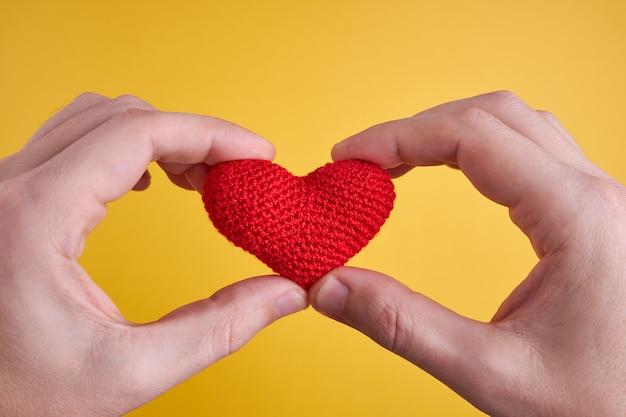 Symbole du coeur à la main des personnes sur le jaune. concept d'amour et de romance