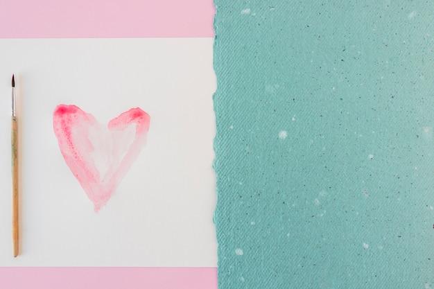 Symbole du coeur sur papier blanc, pinceau et feuille bleue