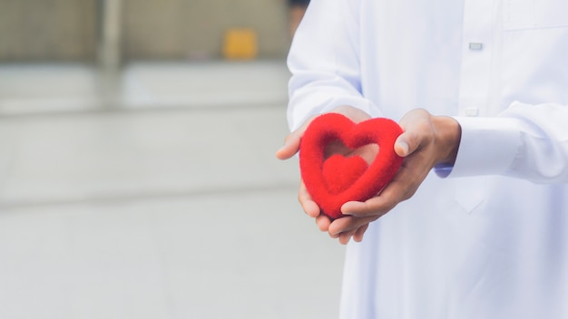 Le symbole du coeur rouge sur la main du prêtre ou de la main de l'homme.
