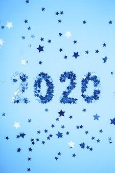 Symbole du nouvel an 2020 de confettis or sur fond bleu.