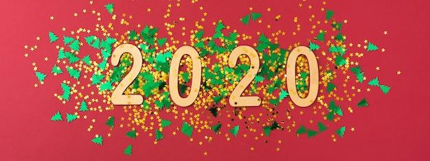 Symbole du numéro 2020 sur rouge avec des confettis or et vert.