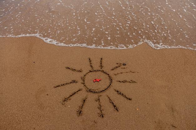 Symbole du soleil et d'un avion au bord de la mer. soleil peint sur le sable, côte de la mer, figure d'un avion rouge, vagues de la mer.