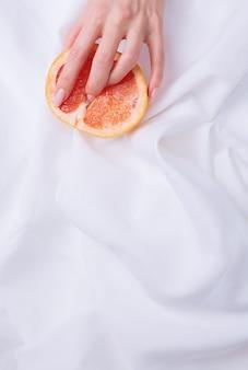 Symbole du vagin. doigts sur le pamplemousse sur fond blanc. notion de sexe.