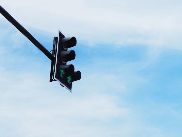 Symbole de la flèche verte sur le feu contre le ciel bleu