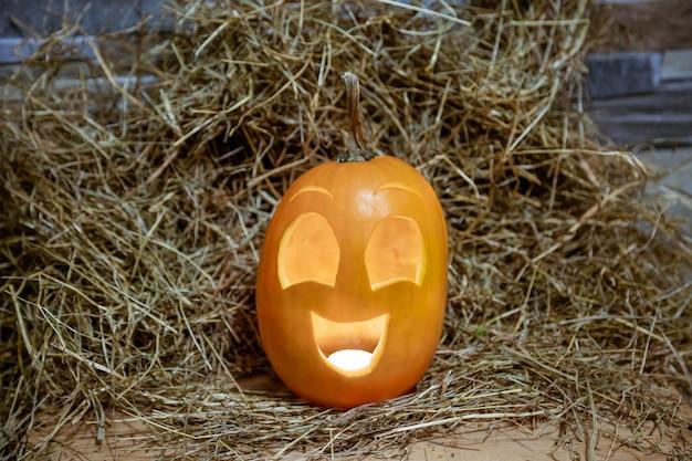 Symbole d'halloween citrouille souriant jaune et heureux sur la lanterne jack o hay avec éclairage de l'intérieur