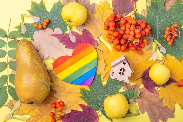 Symbole lgbt de coeur arc-en-ciel en papier et symbole de maison en bois de famille sur des feuilles d'automne sèches multicolores rouges, oranges et vertes et des baies de sorbier orange, des pommes et des poires sur fond jaune.
