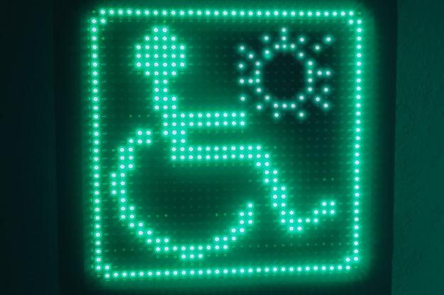 Symbole lumineux vert des handicapés accroché au mur