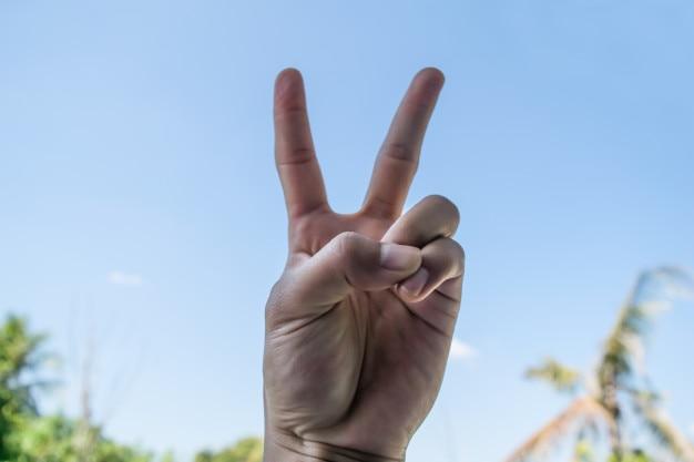 Le symbole de la main deux doigts sur fond de ciel bleu