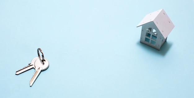Symbole de la maison en bois blanc et clés sur bleu