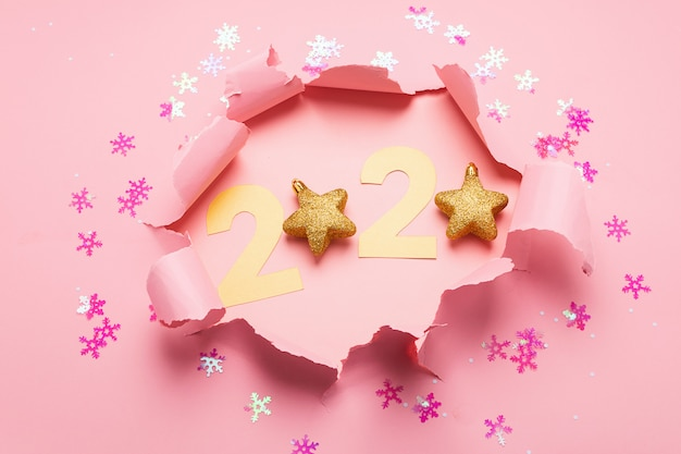 Le symbole de la nouvelle année du numéro 2020 et un trou sur un fond de papier rose.
