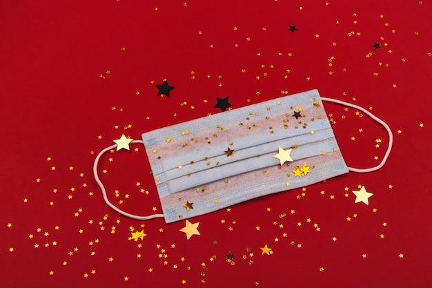 Symbole de pandémie de coronavirus de masque de protection avec des étincelles festives et des étoiles sur fond rouge