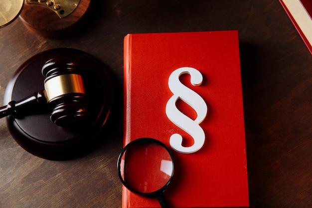 Symbole de paragraphe blanc sur un livre rouge et juge marteau au bureau de l'avocat. vue de dessus