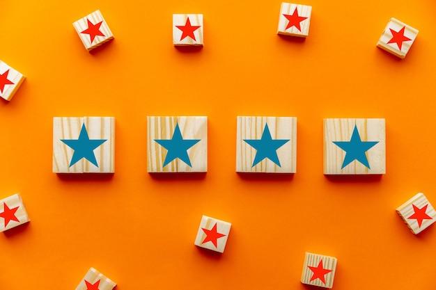 Symbole quatre étoiles sur des cubes en bois sur fond bleu. expérience client, enquête de satisfaction, évaluation, augmentation de la note et meilleurs concepts de notation d'excellents services
