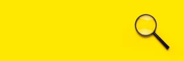 Symbole de recherche de loupe en forme de loupe sur une surface jaune avec espace de copie. bannière.