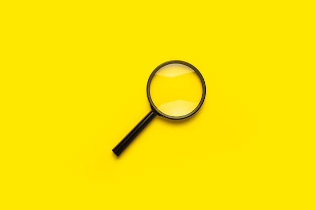 Symbole de recherche de loupe en forme de loupe sur une surface jaune avec espace de copie.