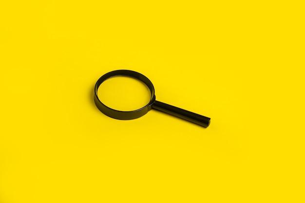 Symbole de recherche de loupe loupe sur une surface jaune. vue de dessus, mise à plat.