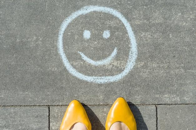 Symbole de smiley heureux dessiné sur l'asphalte