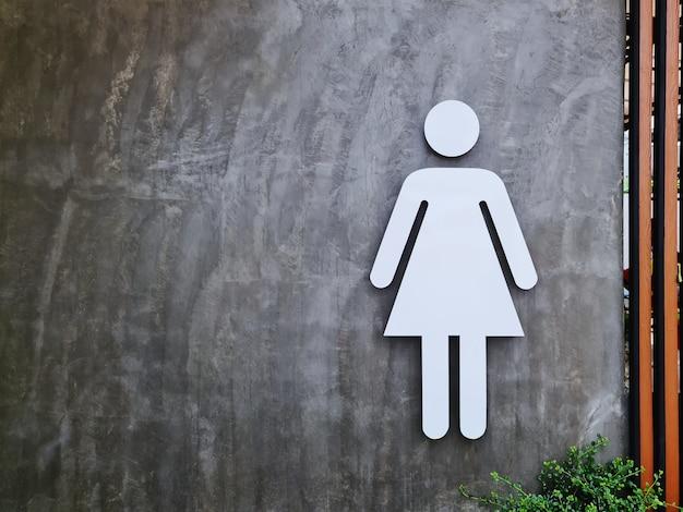 Symbole de toilette des femmes blanches sur un mur en béton nu