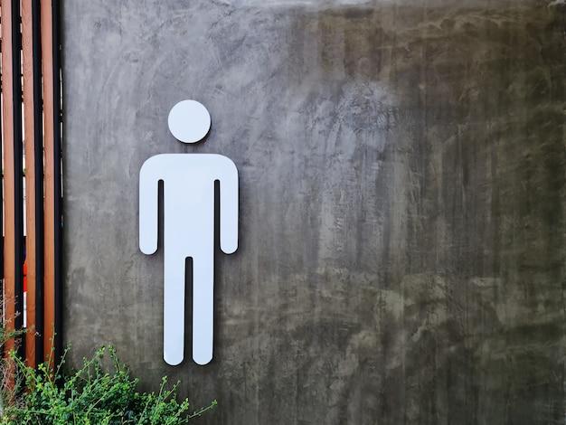 Symbole de toilettes pour hommes blancs sur un mur en béton nu