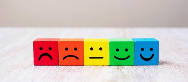 Symbole de visage d'émotion sur des cubes en bois. notation de service, classement, avis client, satisfaction et concept de rétroaction.