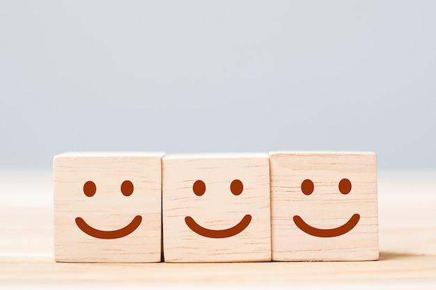 Symbole de visage de sourire sur des blocs de cube en bois. émotion, évaluation du service, classement, avis client, concept de satisfaction et de rétroaction